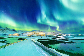 Foto auf Leinwand Insel Amazing view on natural wonder Northern Lights or Aurora Borealis over lighting Kubholmenleia bridge crossing the fjord. Lofoten Islands Archipelago in Norway, location over Polar Circle.