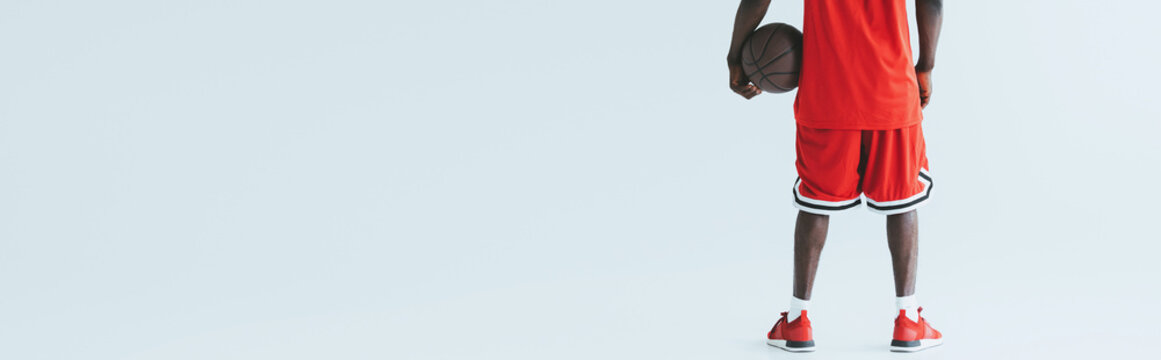 cropped view of african american basketball player holding ball on grey background, panoramic shot