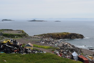 garbage dump site and metal scrap area near the oceans shoreline