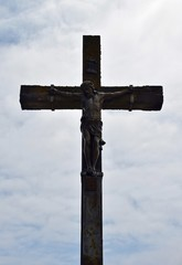 looking up at a large cross with the body of Jesus, backlit