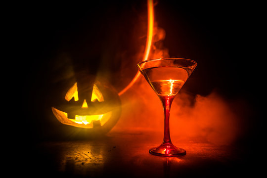 Halloween pumpkin orange cocktails. Festive drink. Halloween party. Funny Pumpkin with a glowing cocktail glass on a dark toned foggy background.