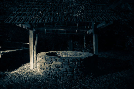 Abandoned well in the forest. Slider shot. Waiting for a terrible girl with a long hair.