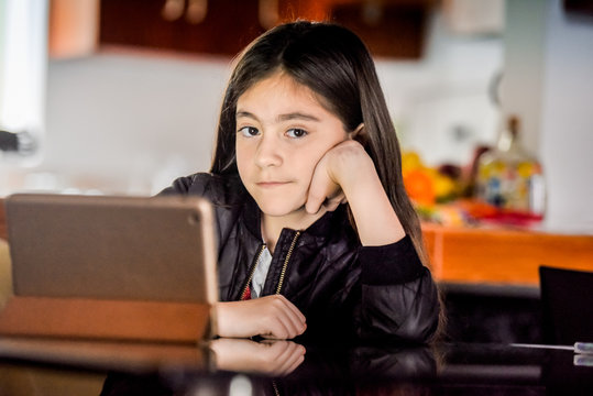 10 years latin girl watching the tablet.