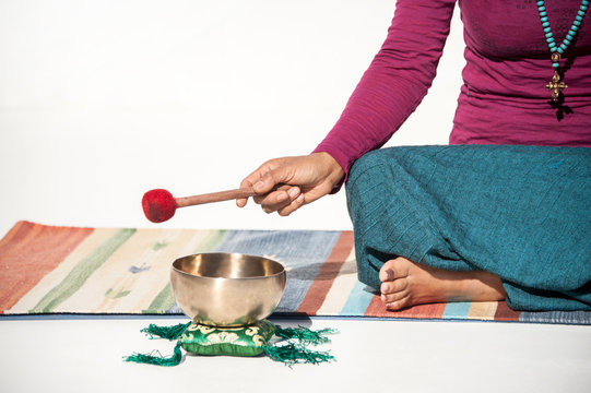 Tibetan Bowl Sound Healing woman yogi hand with mallet photographed on a white background