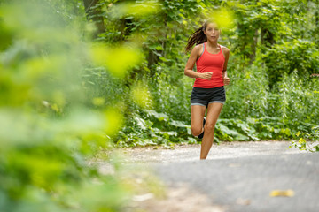 Asian fit girl jogging in park. Young woman running on forest path nature outdoor exercise training cardio workout.
