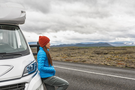 RV camper trailer travel woman driving motorhome camping van on Iceland road trip. Asian tourist driver taking break on adventure fall autumn vacation looking at nature landscape.