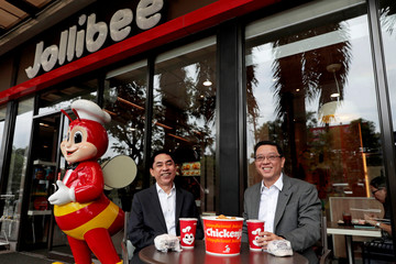 Ernesto Tanmantiong, the president and CEO of Philippine national champion Jollibee Foods Corp, and Ysmael Baysa, its CFO, pose for a picture outside a Jollibee branch in Pasig City,