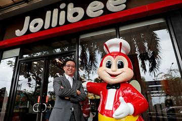 Ernesto Tanmantiong, the president and CEO of Philippine national champion Jollibee Foods Corp., poses for a picture beside a Jollibee mascot outside a Jollibee branch in Pasig City