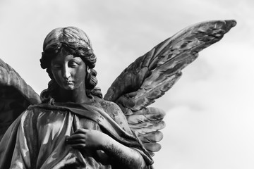 Sad angel sculpture with open long wings across the frame against a bright white sky. The sad expression sculpture with eyes down and hand in front of chest. Black and white BW photography.