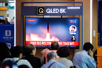 People watch a TV that shows a file picture of a North Korean missile for a news report on North Korea firing short-range ballistic missiles, in Seoul