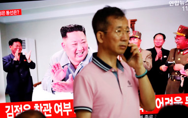 A man stands near a TV showing a file picture of North Korean leader Kim Jong Un for a news report on North Korea firing short-range ballistic missiles, in Seoul