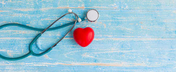 Red heart and stethoscope on vintage wooden blue background