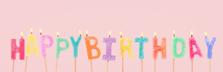 Cute pastel colorful happy birthday font candles with flames on pink background.