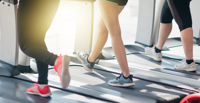 Cropped photo of female legs in sportswear and sneakers running on a treadmill in the gym against the window