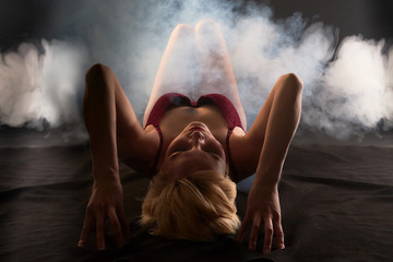 Sexy blonde girl during professional photo shoot in dark room with smoke. Model in a red swimsuit