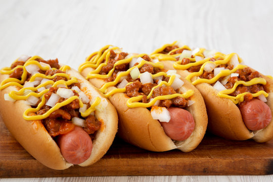 Homemade Coney Island hot dog on a rustic wooden board on a white wooden background, side view. Close-up.