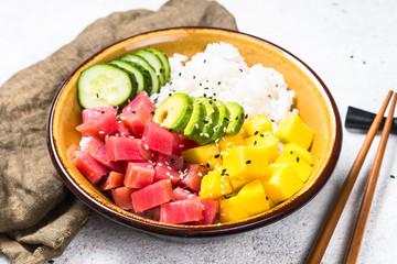 Tuna poke bowl with rice, avocado, mango and cucumber on white table.