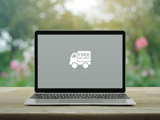 Free delivery truck flat icon with modern laptop computer on wooden table over blur pink flower and tree in garden, Business transportation online concept