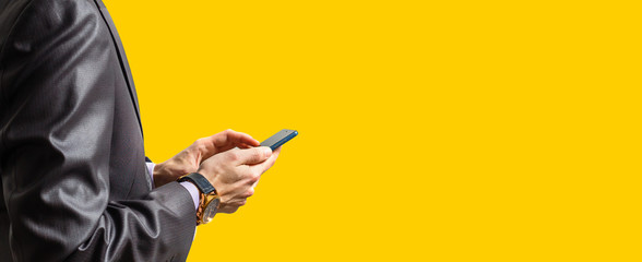 Hands of businessman calling by phone yellow background