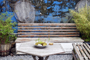 Vintage wooden benches and table in a garden with green plants and rustic wall. Wood patio furniture in a vintage backyard
