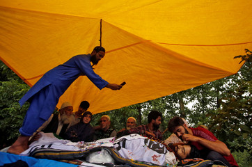 A man takes pictures of the body of Fayaz Ahmad Thokar, a suspected militant commander who according to local media was killed in a gun battle with Indian security forces on Tuesday, before his funeral prayers in south Kashmir's Tral town