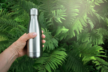 Reusable stainless thermos bottle for water in female hand.
