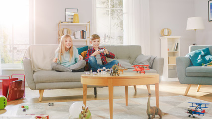 At Home: Smart Boy Playing in Video Game Console, Using Joystick Controller, His Older Sister Sits Near on Sofa and Cheers for Him. Happy Children Playing Videogames Together.