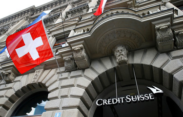 Switzerland's national flag flies below a logo of Swiss bank Credit Suisse in Zurich