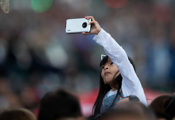 Young fan takes a mobile phone picture at The Opening Ceremony of The Youth Olympic Games, Buenos Aires, Argentina,