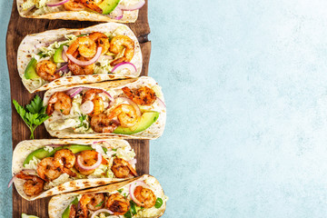 Shrimp tacos. Seafood fajitas with cabbage, onion, parsley in tortillas served on wooden cutting board. blank space for a text food background