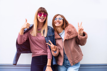 Picture of two playful girls standing together and showing peace gestures while looking at the camera over white background outdoor