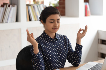Concentrated indian girl meditating with closed eyes at workplace