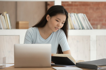 Focused Asian girl prepare for exam with book and laptop