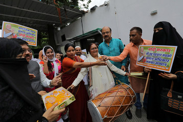 Muslim women along with supporters of India's ruling BJP distribute sweets to celebrate after India's parliament approved a bill on Tuesday outlawing the centuries-old right of a Muslim man to instantly divorce his wife, in New Delhi