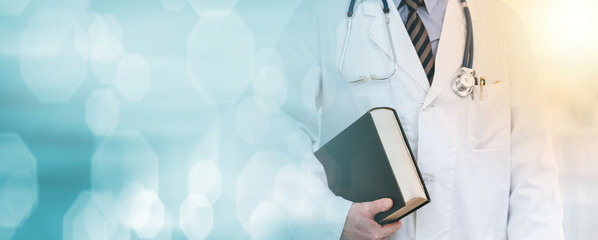 Doctor holding a medical textbook; light effect