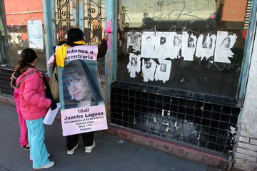 A woman carries a photograph of a missing woman on her back while she paints an area of a wooden frame pink next to photographs of missing women in Ciudad Juarez