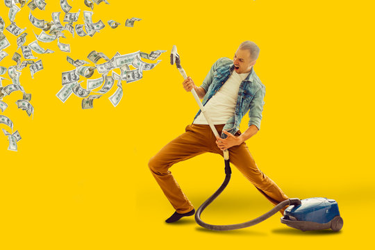 Young man having fun cleaning house with vacuum cleaner man collects money Vacuum