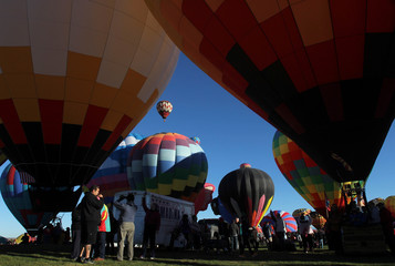Visitors take pictures of hot air balloons before they take flight during the 42nd annual Albuquerque International Balloon Fiesta in Albuquerque