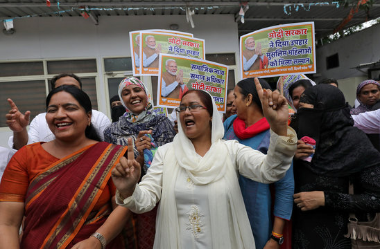 Muslim women along with supporters of India's ruling BJP celebrate after India's parliament approved a bill on Tuesday outlawing the centuries-old right of a Muslim man to instantly divorce his wife, in New Del