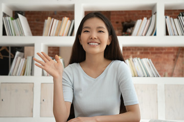 Smiling Asian girl greeting waving having video call