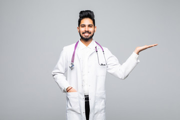Handsome indian man doctor presenting something standing isolated over blue background