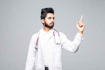 A portrait of a happy male doctor pointing at a copy space isolated on white background