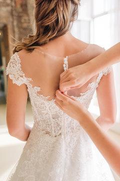 hands help the bride to zip up put on the  wedding dress