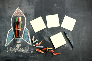 School blackboard background with some stationery and school supplies. Chalk drawing in white and...