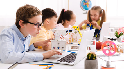 Schoolboy programming diy robot with laptop at stem lesson