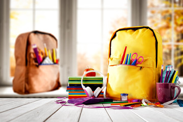 Schoolbags background with some school supplies on wooden desk top and a windowsill with white...