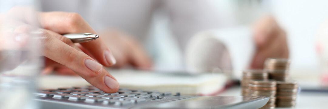 Woman hand push on calculator keyboard