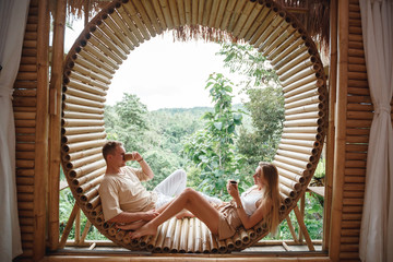 Romantic couple relaxes on a old wooden bungalow veranda, drinks coffee and enjoying life