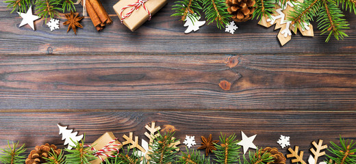 Wall Mural - Christmas background with fir tree and gift box on wooden table. Top view banner with copy space for your design