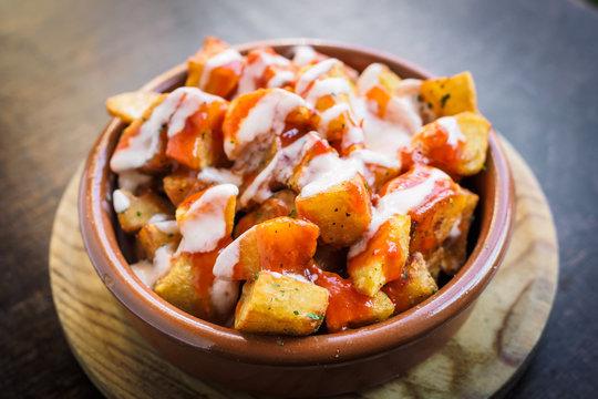 Spanish potatoes patatas bravas for tapas with tomato and spicy sauce
